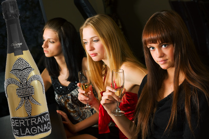 Three young women drinking champagne  in a bar.
